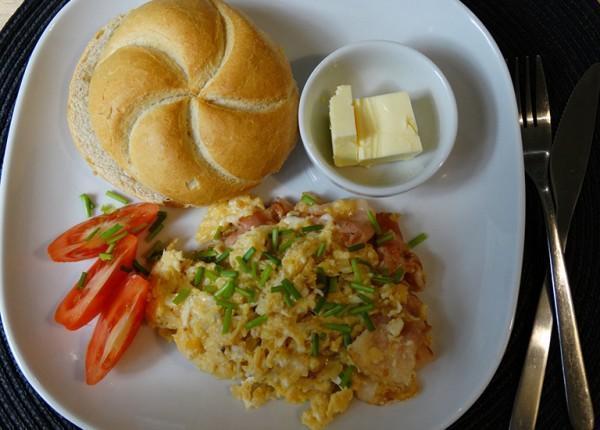jajecznica podana z kajzerką, masłem i pomidorem